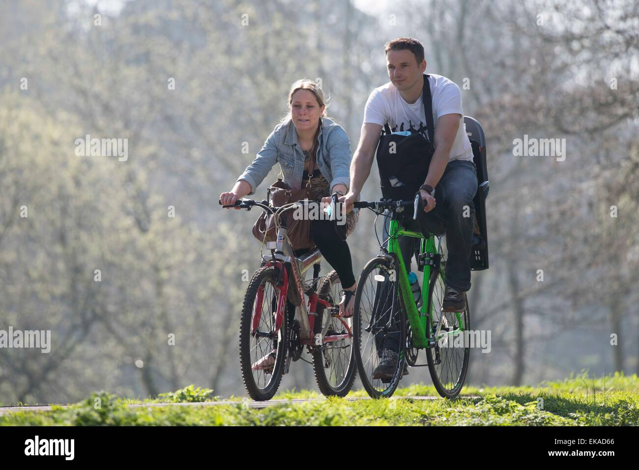 A couple ride their bikes on the Taff Trail in Cardiff, South Wales, during warm sunny weather. - Stock Image