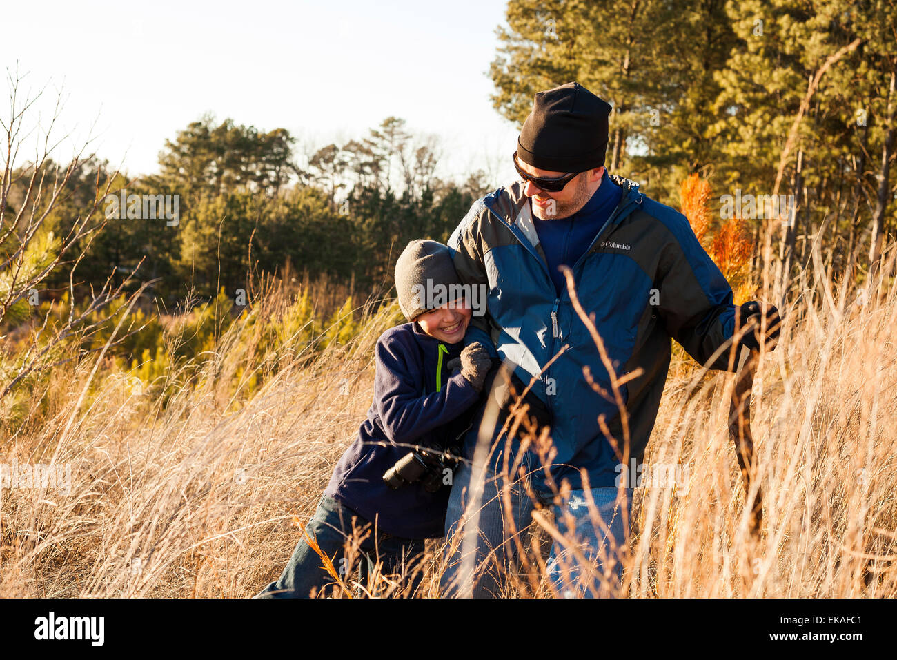 Father and son hiking in field - Stock Image