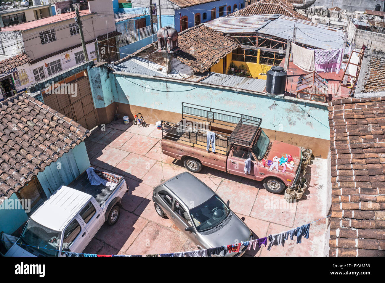 view down on courtyards hidden from street where old truck is seen used as drying surface for clothes overflowing - Stock Image
