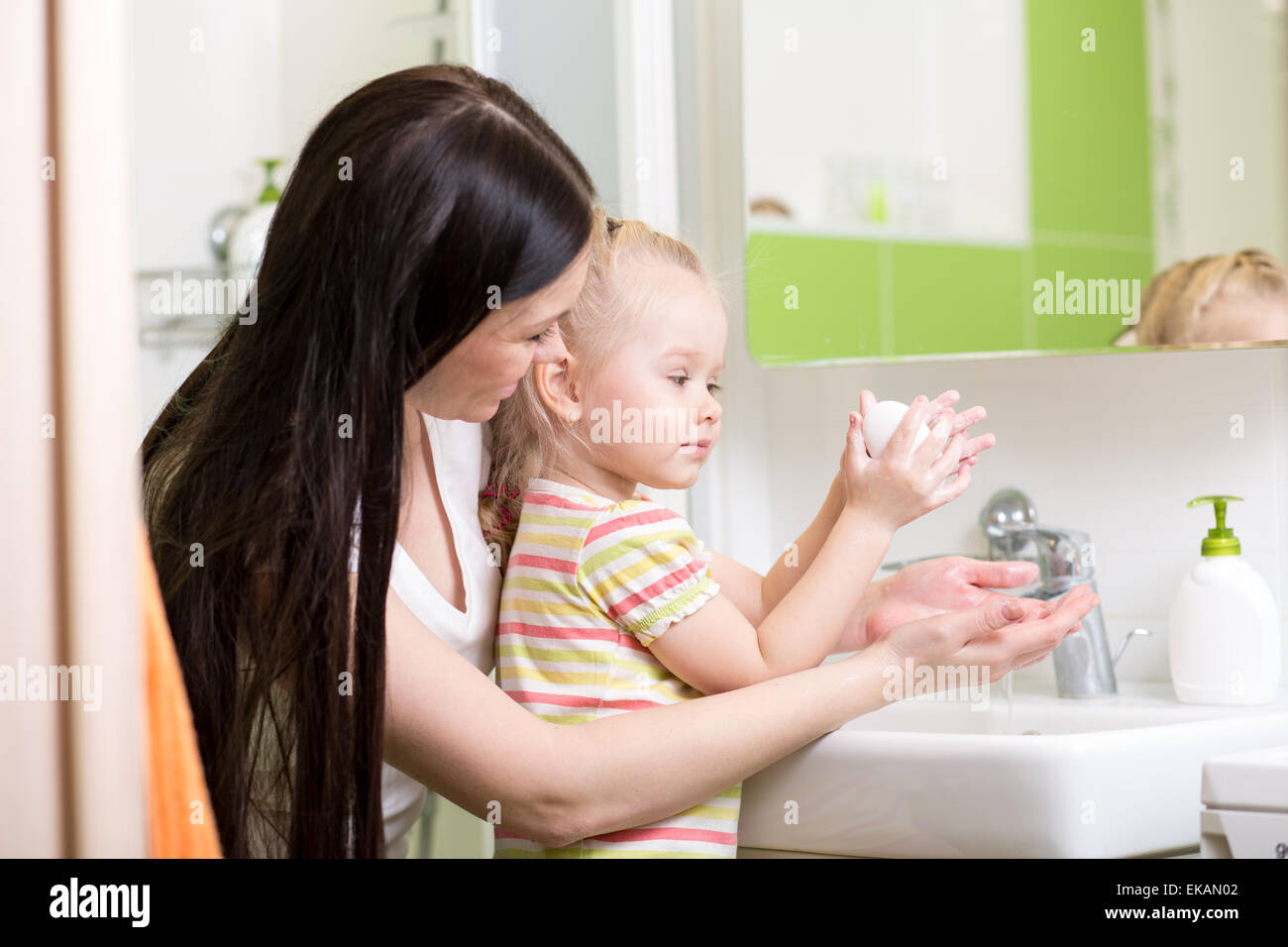 mother teaches kid washing hands in bathroom - Stock Image
