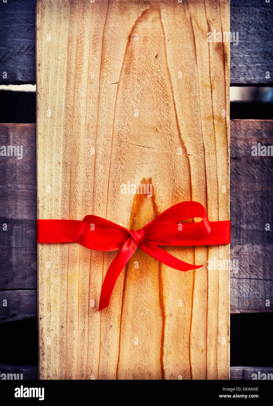 Red Bow And Blank Gift Tag With Wooden Wall Stock Photo