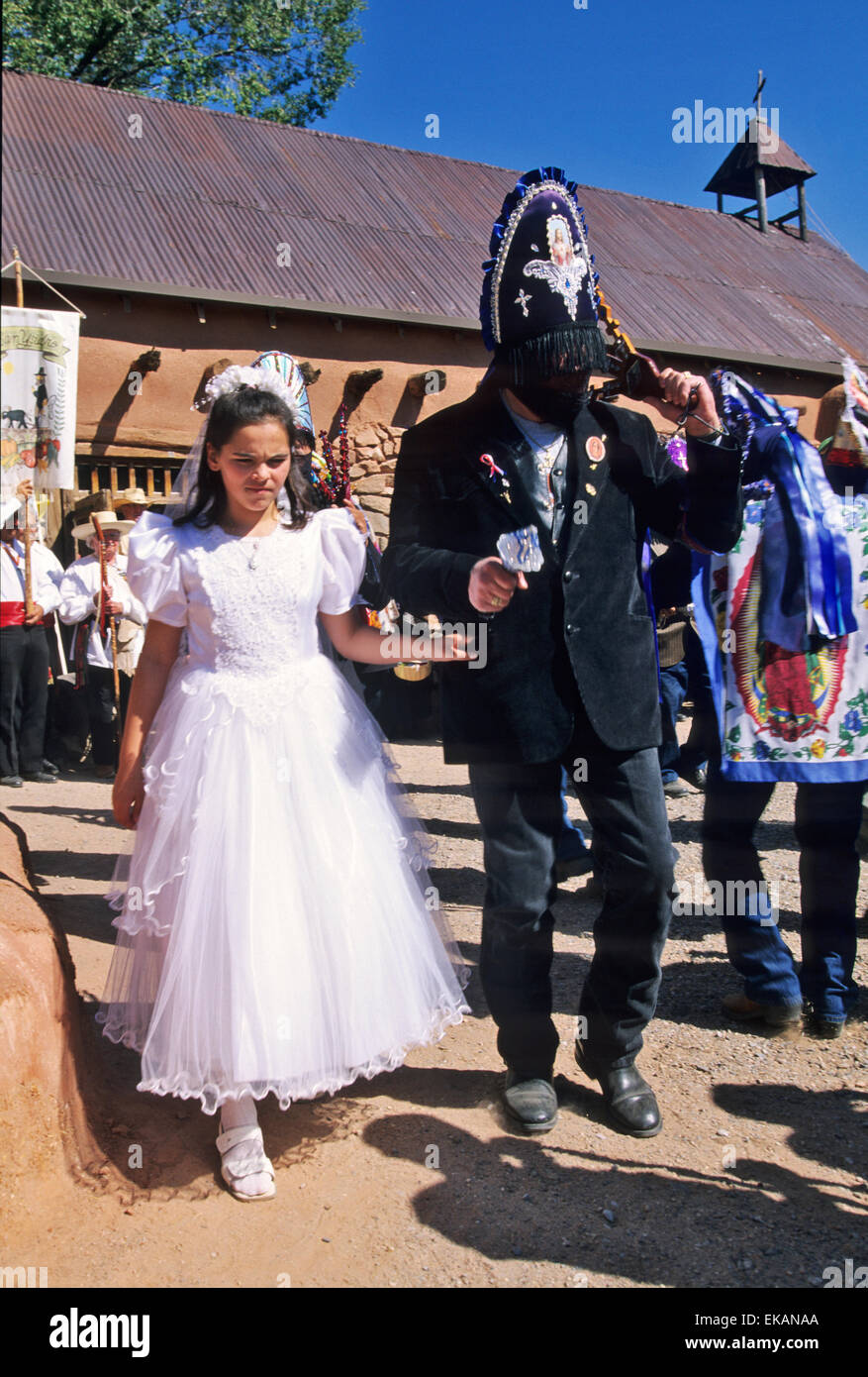 Wearing their veiled headresses and carrying ceremonial tridents, mysterious Matachine dancers and a young girl Stock Photo