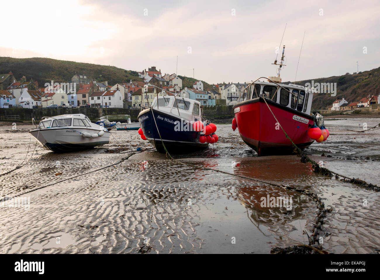 A group of 3 fishing boats on the sand at low tide in Staithes North Yorkshire. Stock Photo