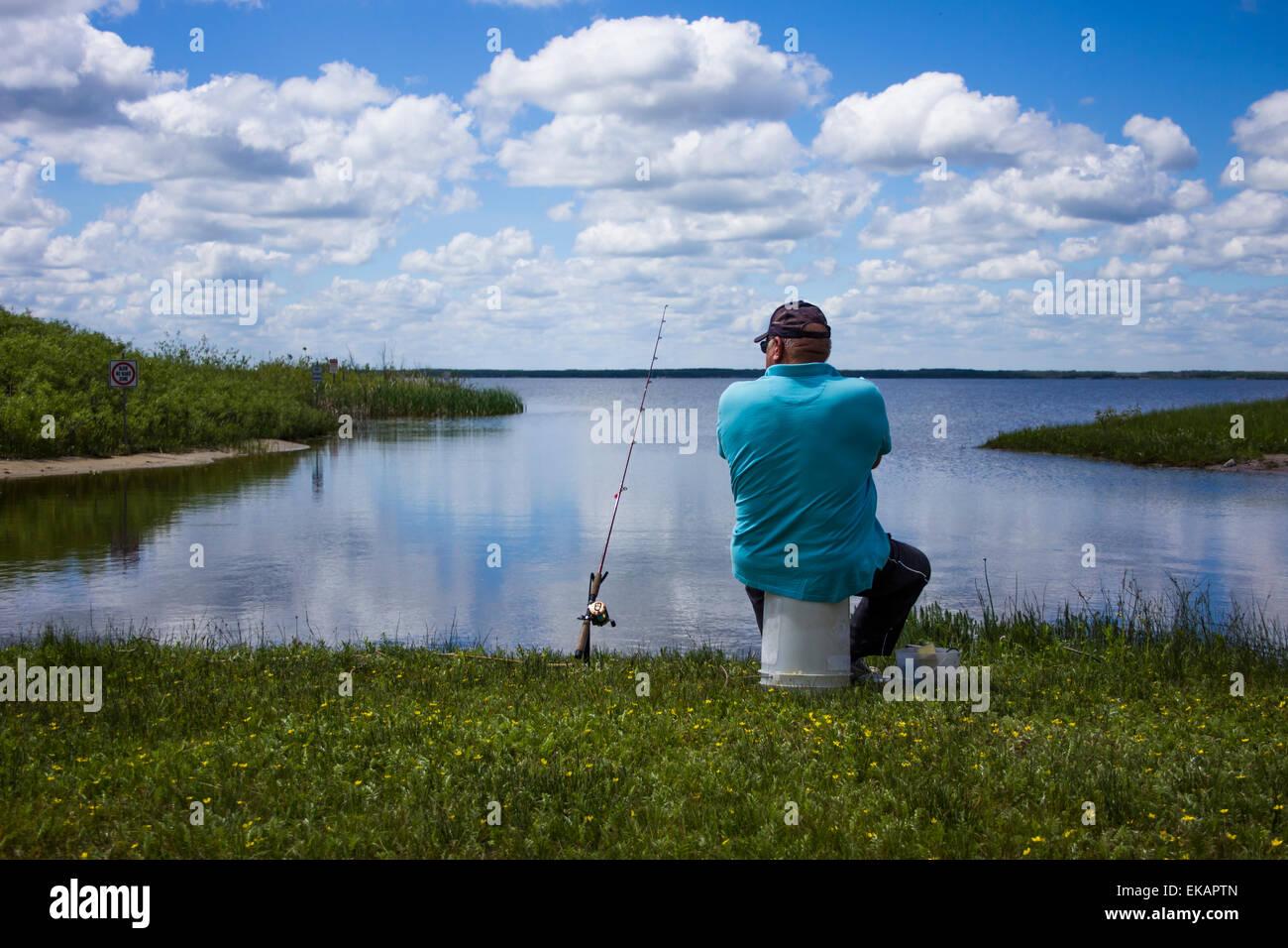 Mature man fishing at calm peaceful country lake. Stock Photo