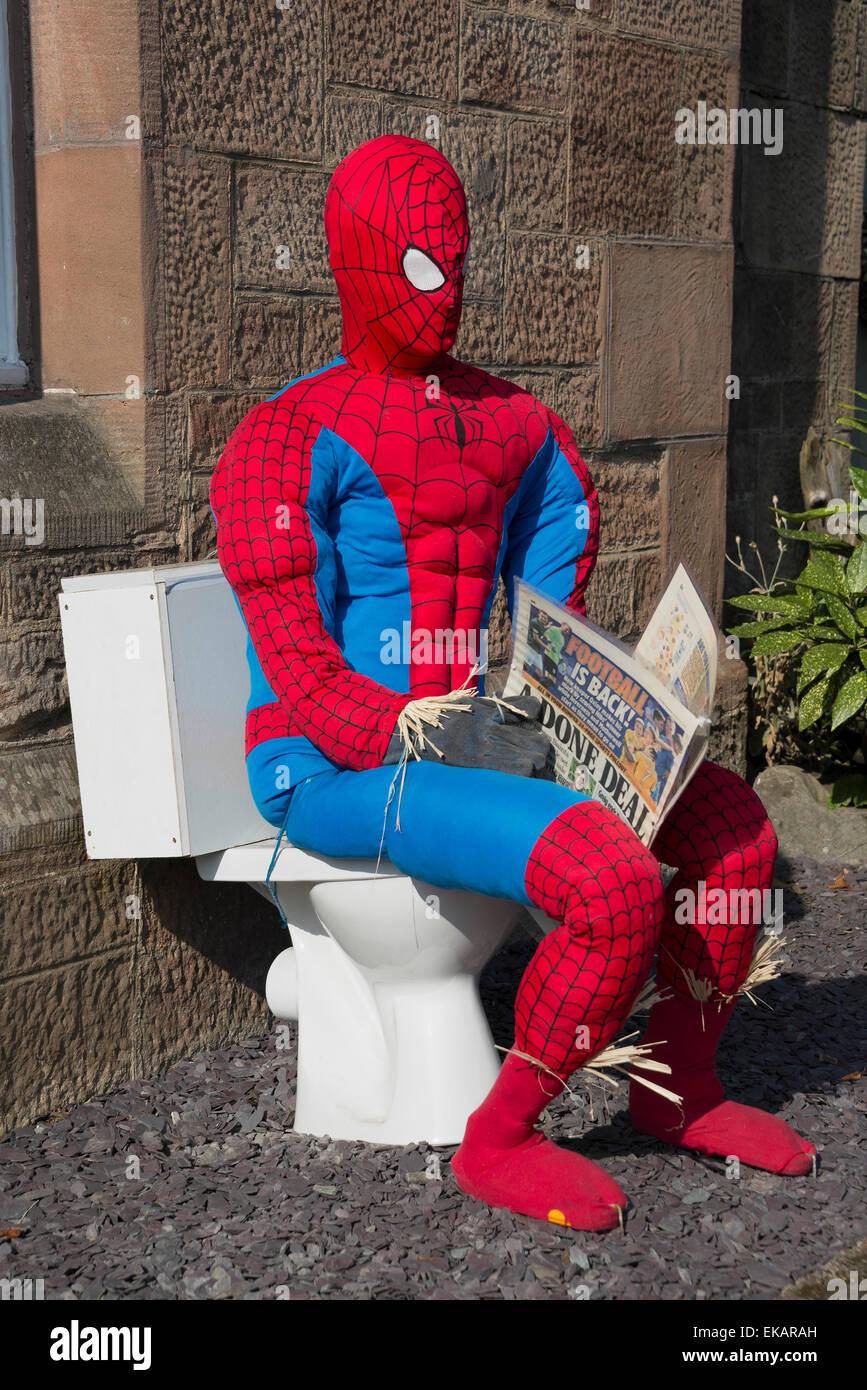 spiderman scarecrow at scarecrow festival sitting on toilet reading newspaper stock image