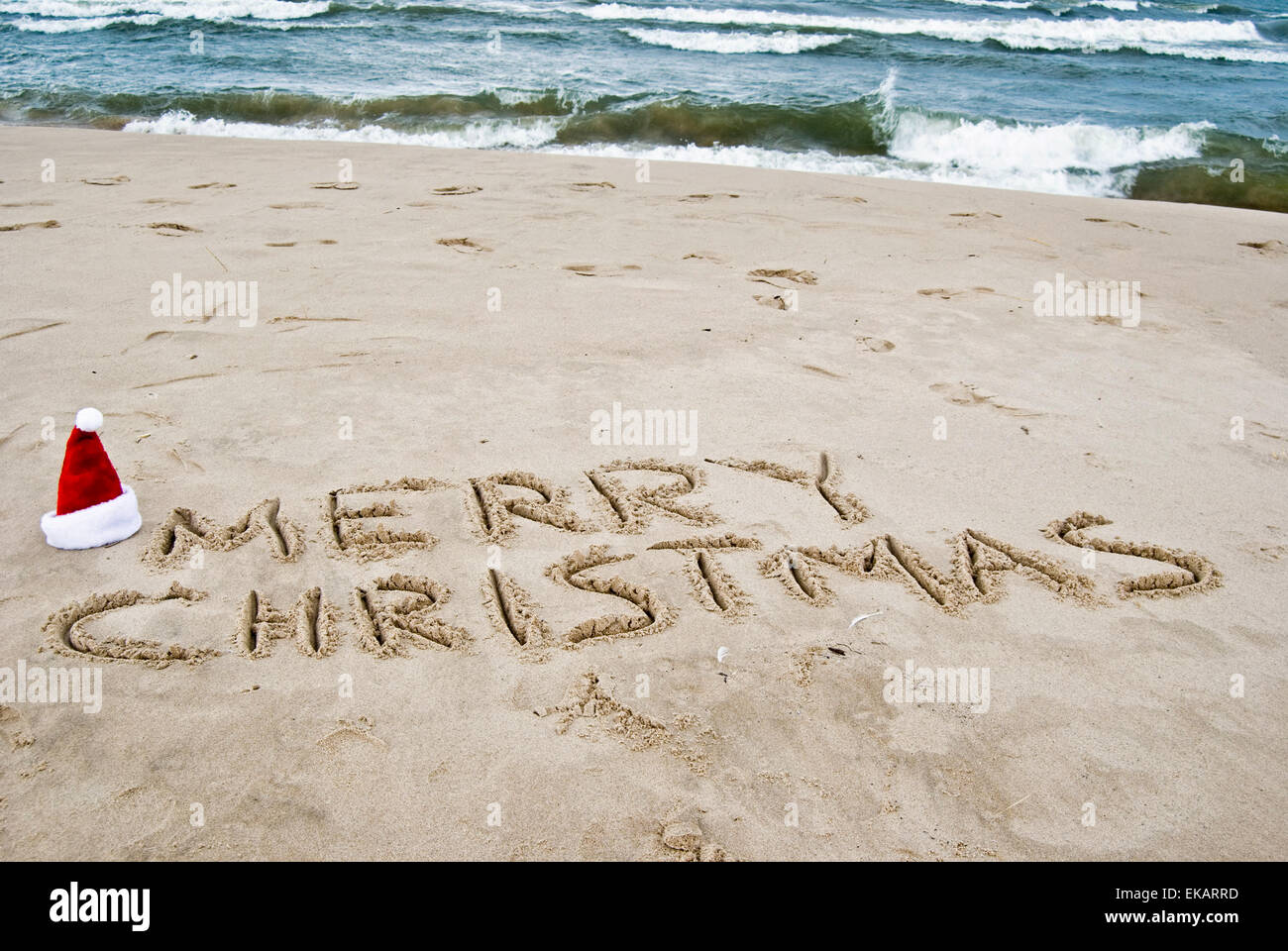 santa hat with merry christmas in beach sand - Merry Christmas Beach Images