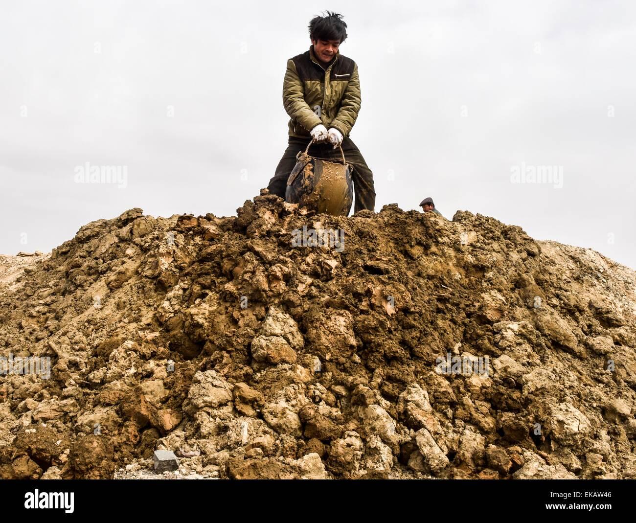 (150409) -- TURPAN, April 9, 2015 (Xinhua) -- Dredging worker Turxun Abdul dumps a 40-kilogram-weight barrel of - Stock Image
