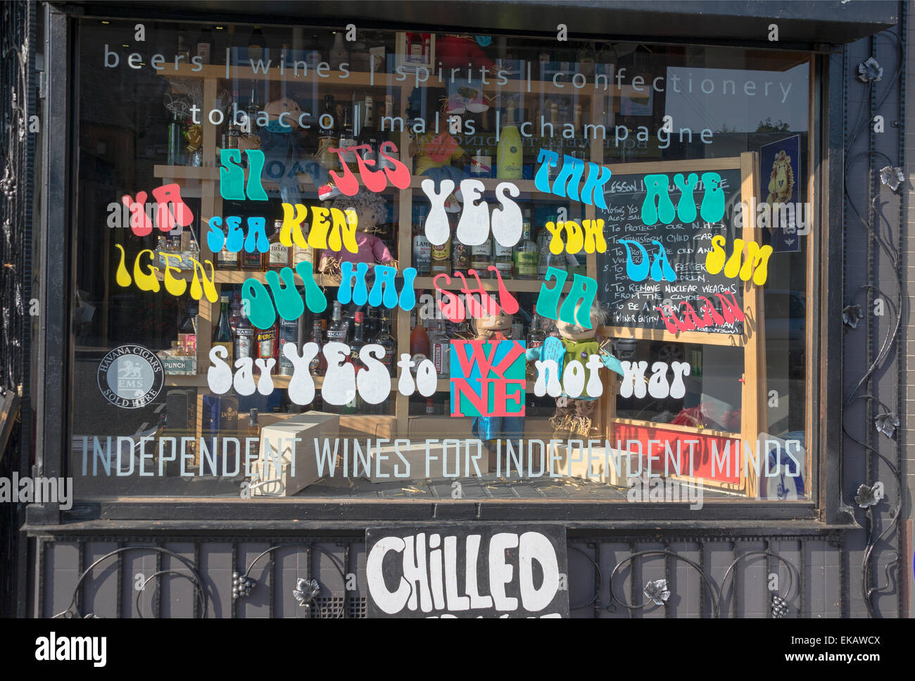 Shop window of wine merchant store displaying the word YES in many languages. - Stock Image