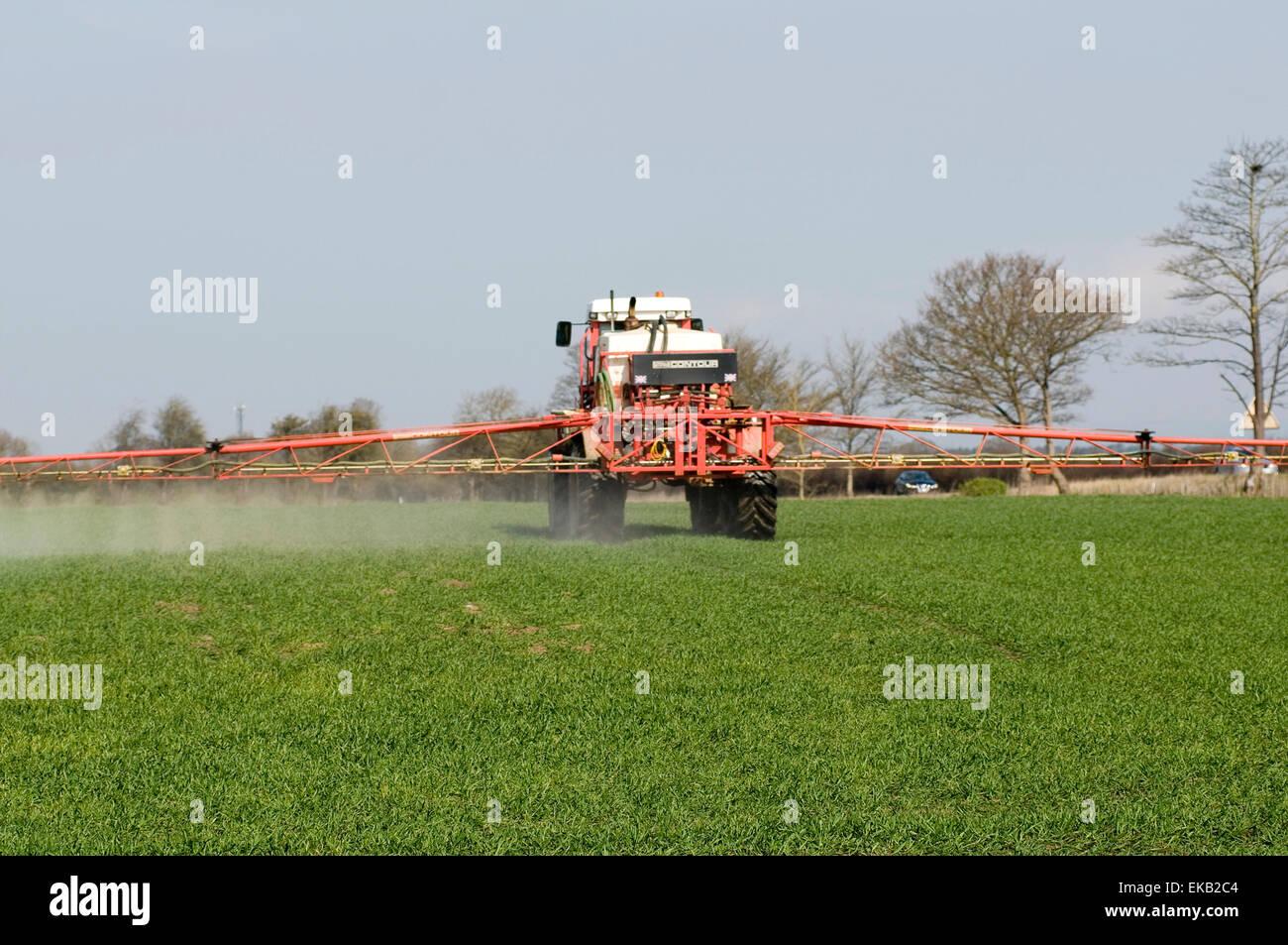 tractor spraying crops crop spraying tractors field fields farm farming farms agriculture farmer farmers pesticide - Stock Image