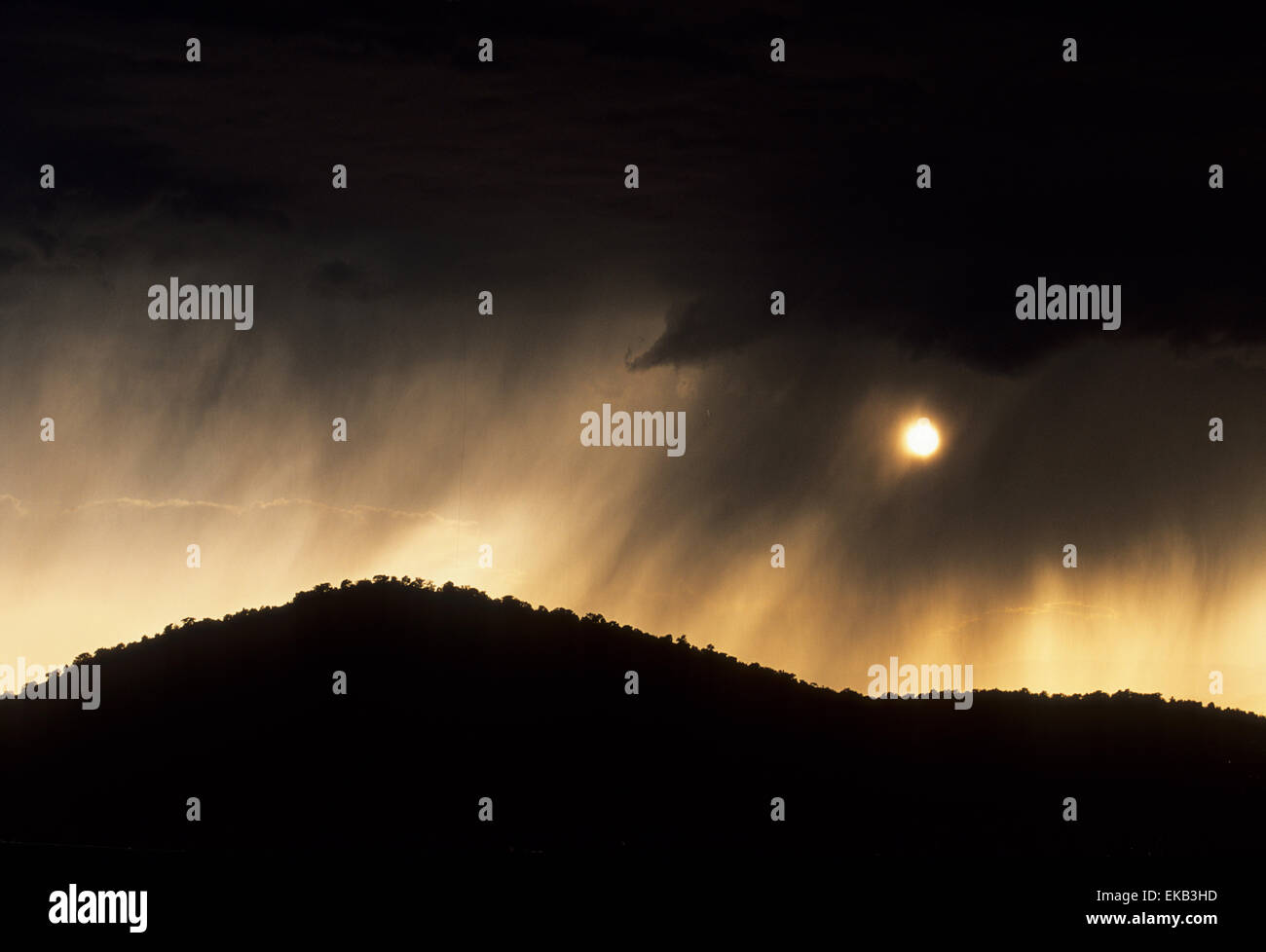 A summer rainstorm is a passing  event in northern New Mexico, where the sun peeks out from below the clouds. - Stock Image