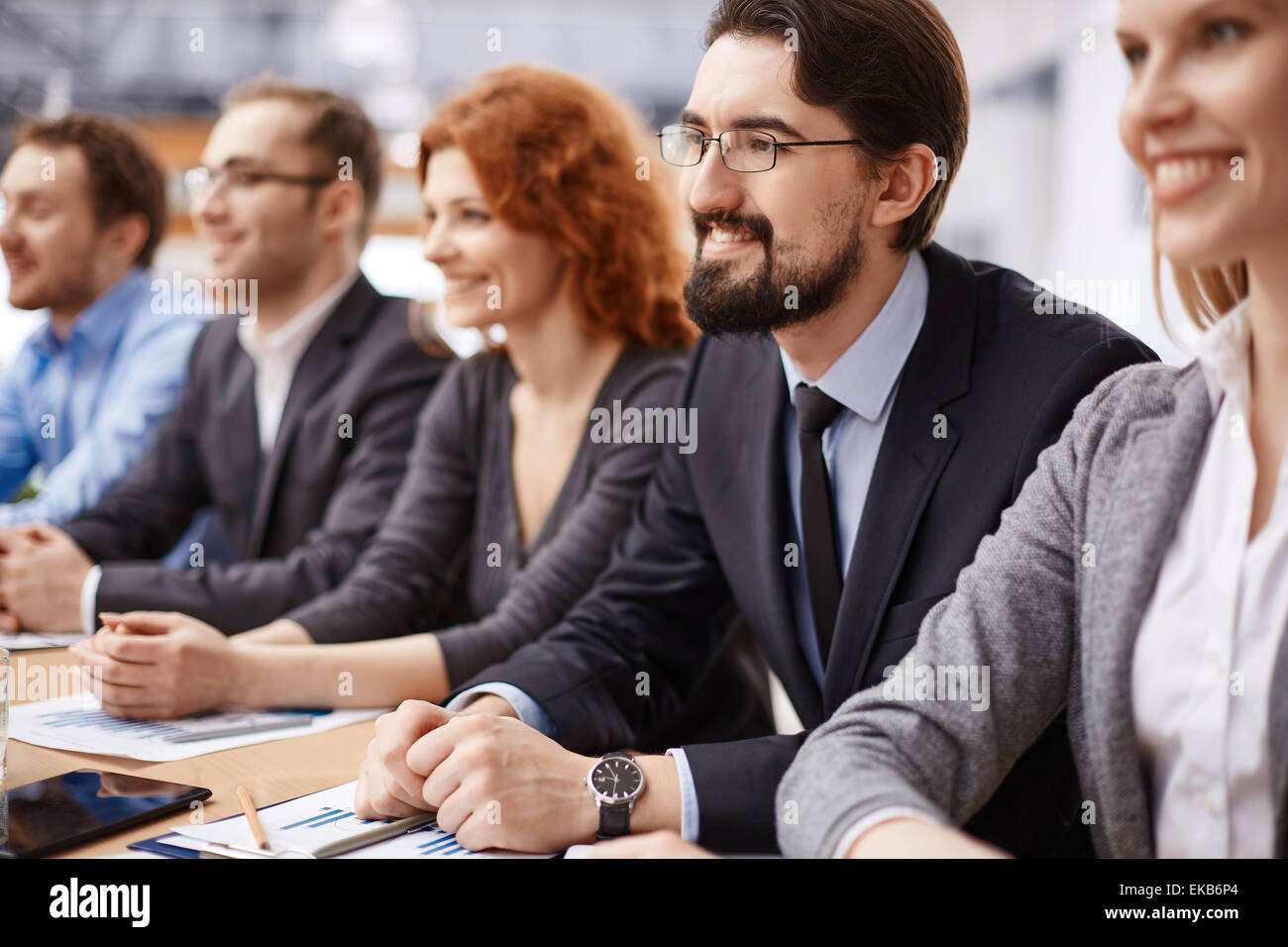 Young businessman listening to speaker among co-workers at conference - Stock Image
