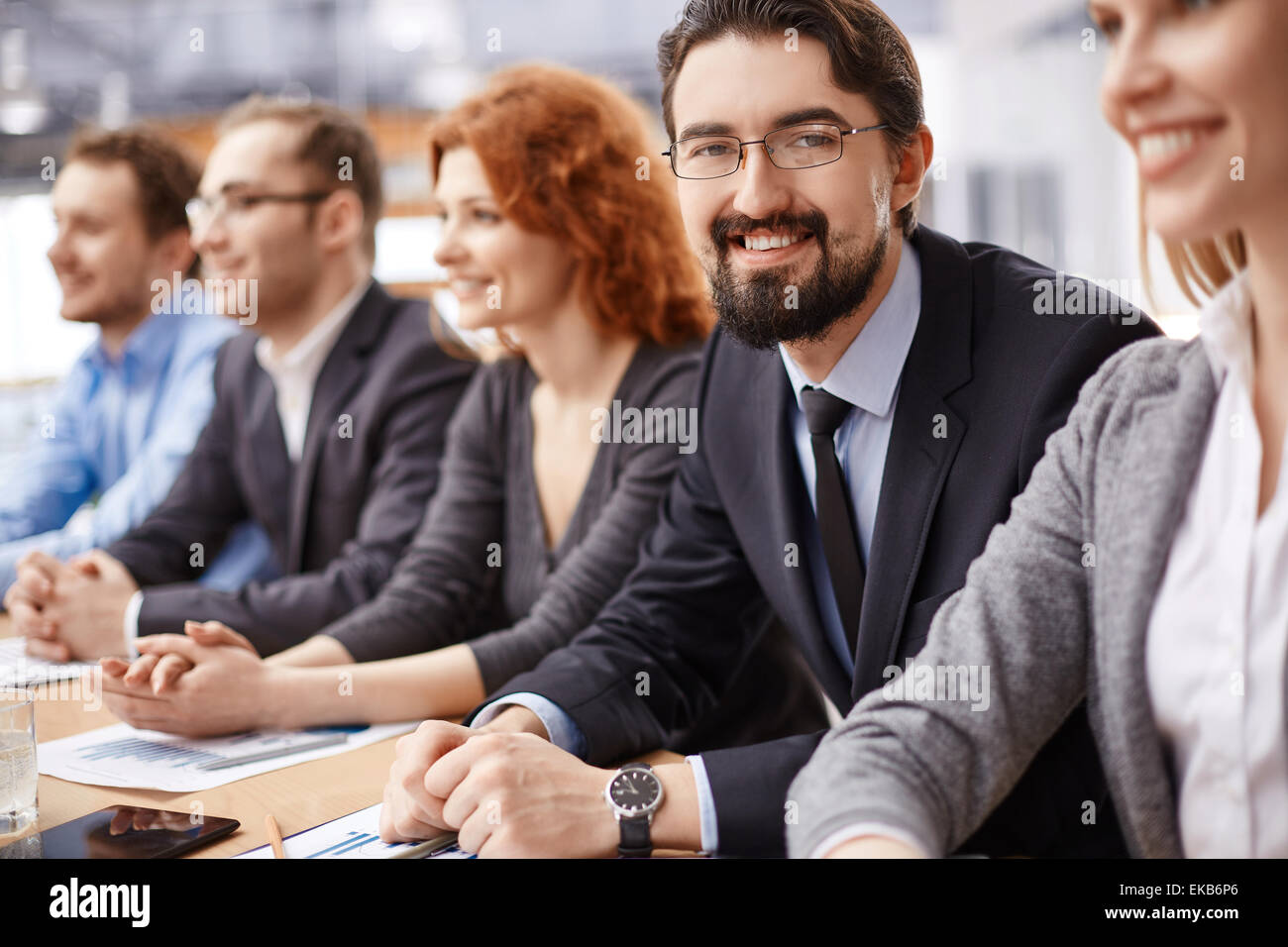 Young businessman sitting among co-workers and looking at camera at conference - Stock Image