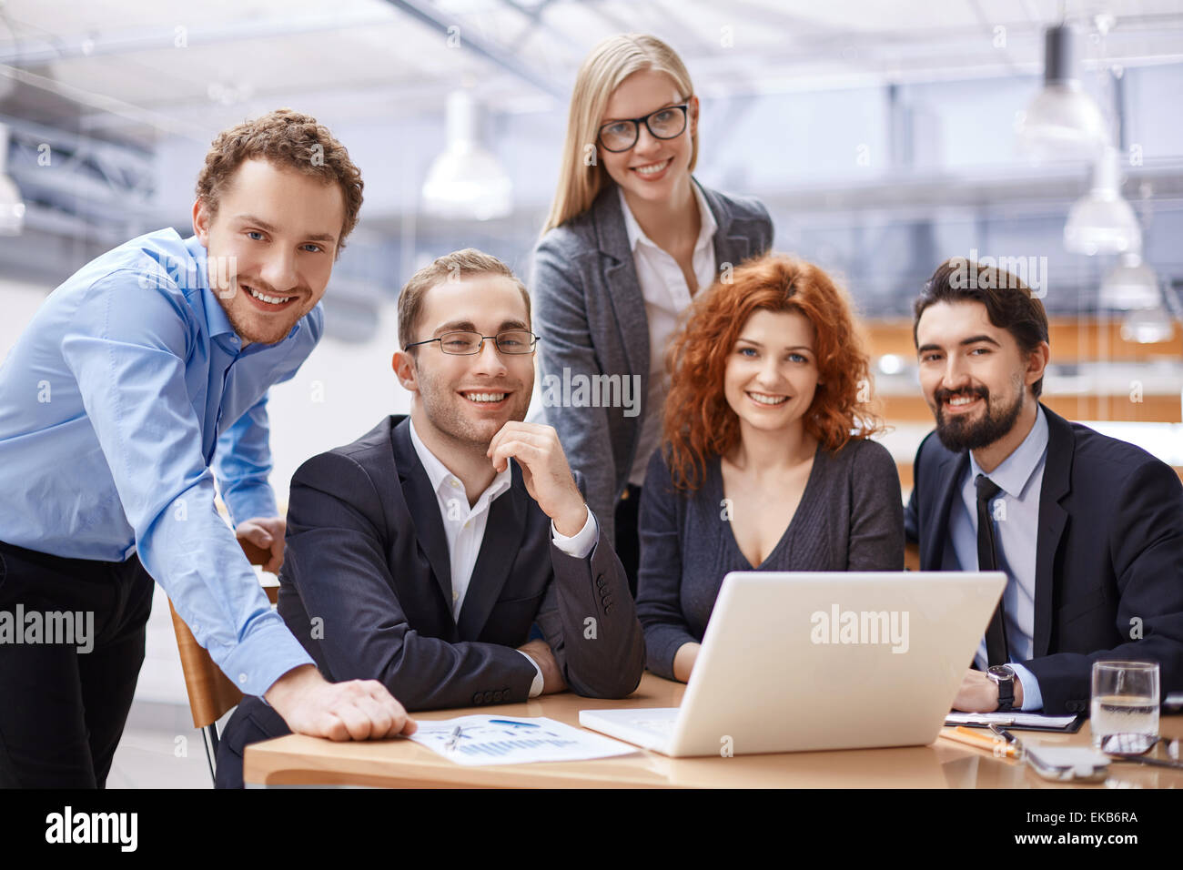 Happy business partners looking at camera with smiles - Stock Image