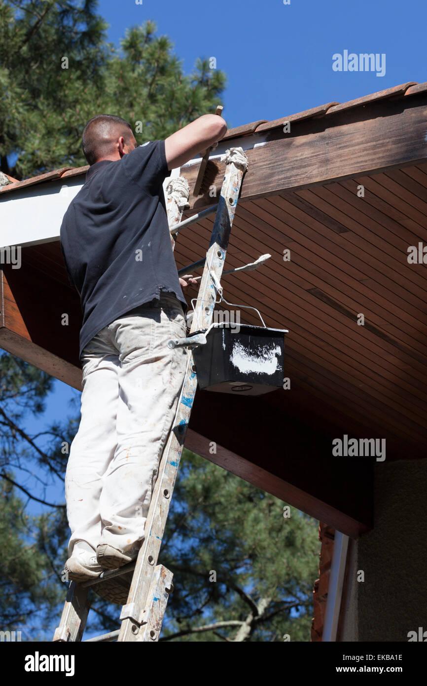 A self-employed house painter at work on eaves (France). Peintre en bâtiment oeuvrant sur l'avant-toit - Stock Image