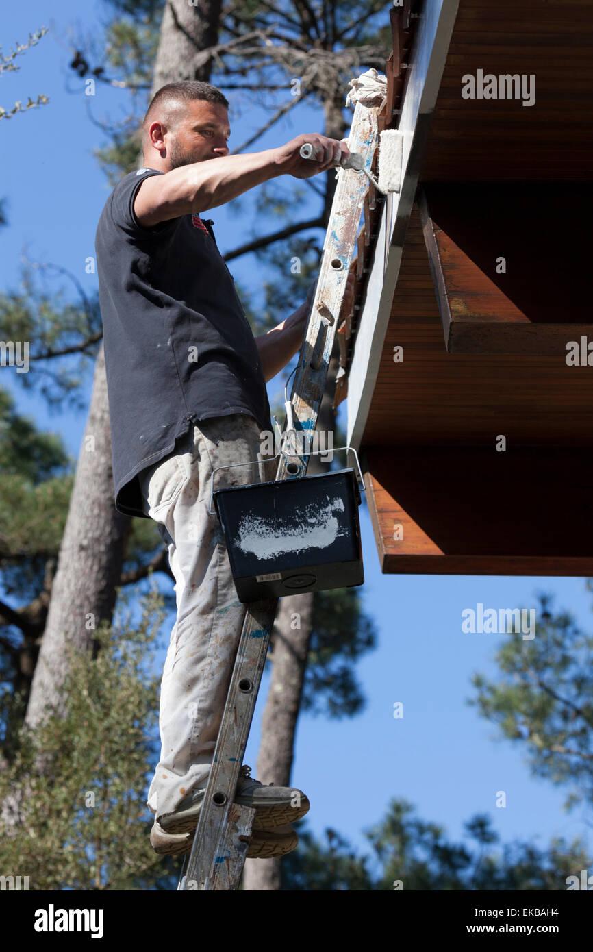 A self-employed house painter at work on eaves (France). Peintre en bâtiment oeuvrant sur les rives d'un - Stock Image