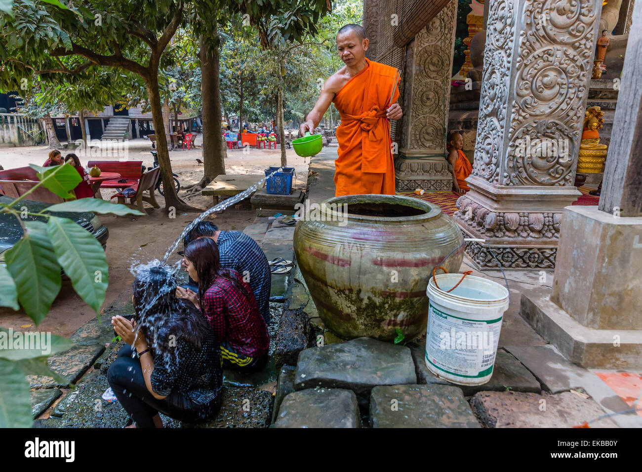 Buddhist monk offers water blessing near Prasat Bayon, Angkor Thom, Angkor, Siem Reap Province, Cambodia, Indochina, Stock Photo