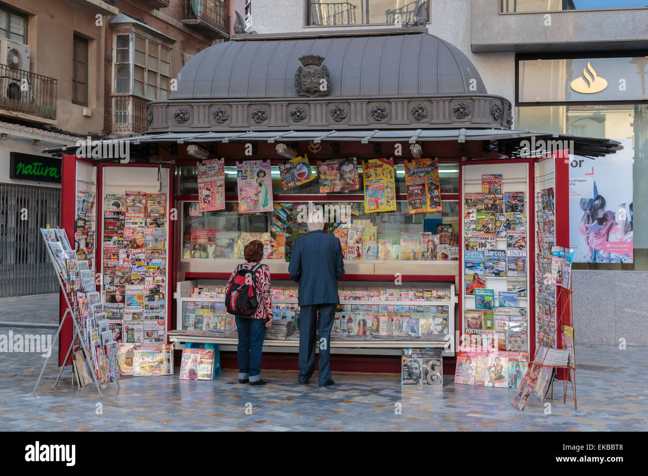 People stand at a red newspaper and magazine kiosk with fancy roof, Cartagena, Murcia Region, Spain, Europe - Stock Image