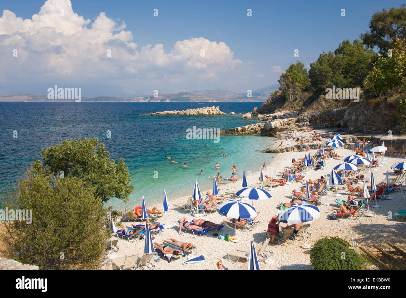 Beach crowded with holidaymakers, Kassiopi, Corfu, Ionian Islands, Greek Islands, Greece, Europe - Stock Image