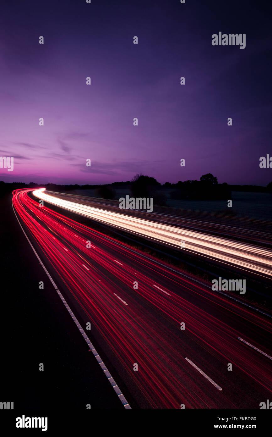 Fast moving traffic on M25 motorway at night, London, England, United Kingdom, Europe - Stock Image