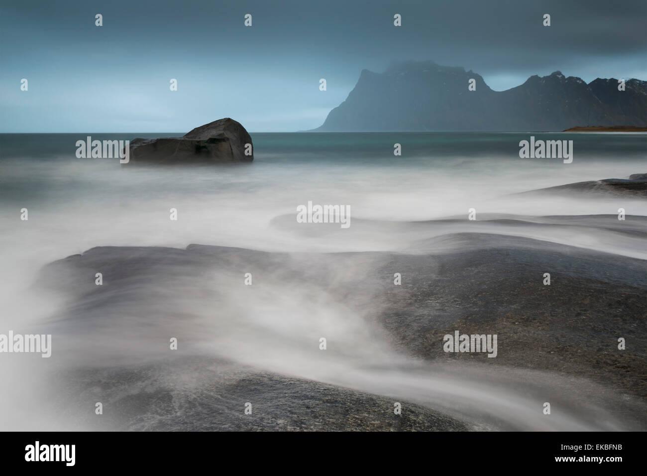 Water breaks over rocks at Uttakleiv, Lofoten Islands, Arctic, Norway, Scandinavia, Europe - Stock Image