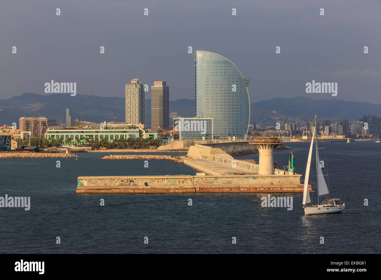Yacht sails past La Barceloneta and the waterfront, Port Olimpic in distance, late afternoon, Barcelona, Catalonia, - Stock Image