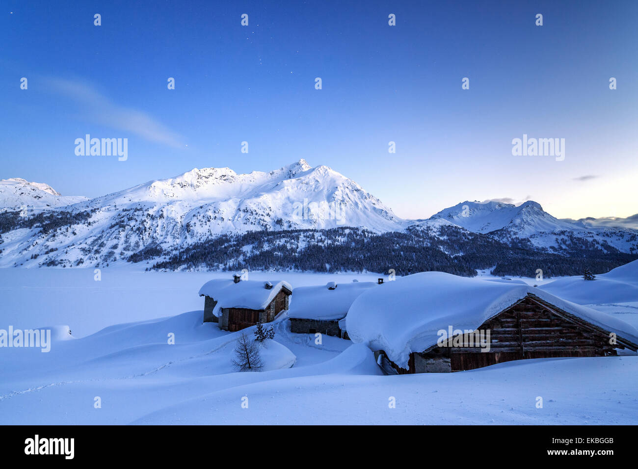 The blue hour leaving its place to the night over some scattered huts in Spluga, Graubunden, Swiss Alps, Switzerland - Stock Image