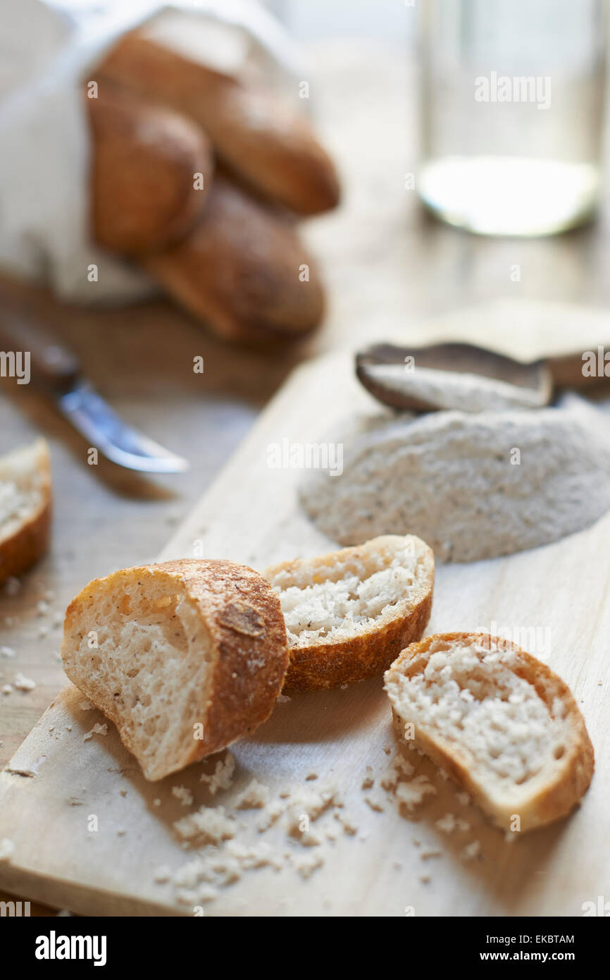Gluten-free baguette slices on cutting board - Stock Image