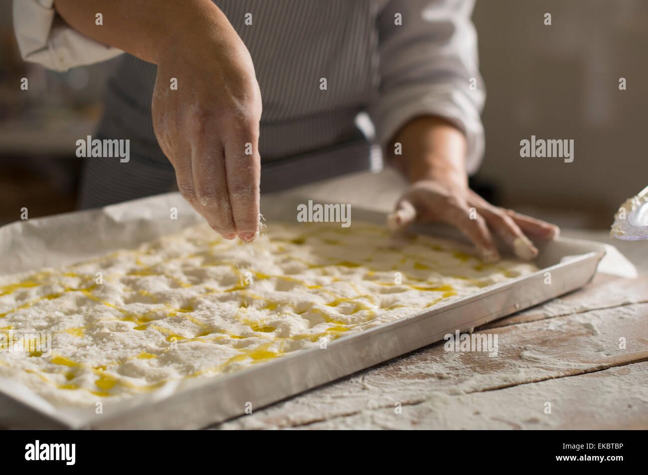 Baker preparing gluten-free dough for baking - Stock Image