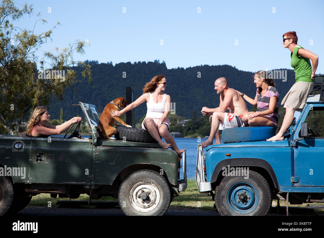 Adult friends chatting on top of off road vehicles, Lake Okareka, New Zealand - Stock Image