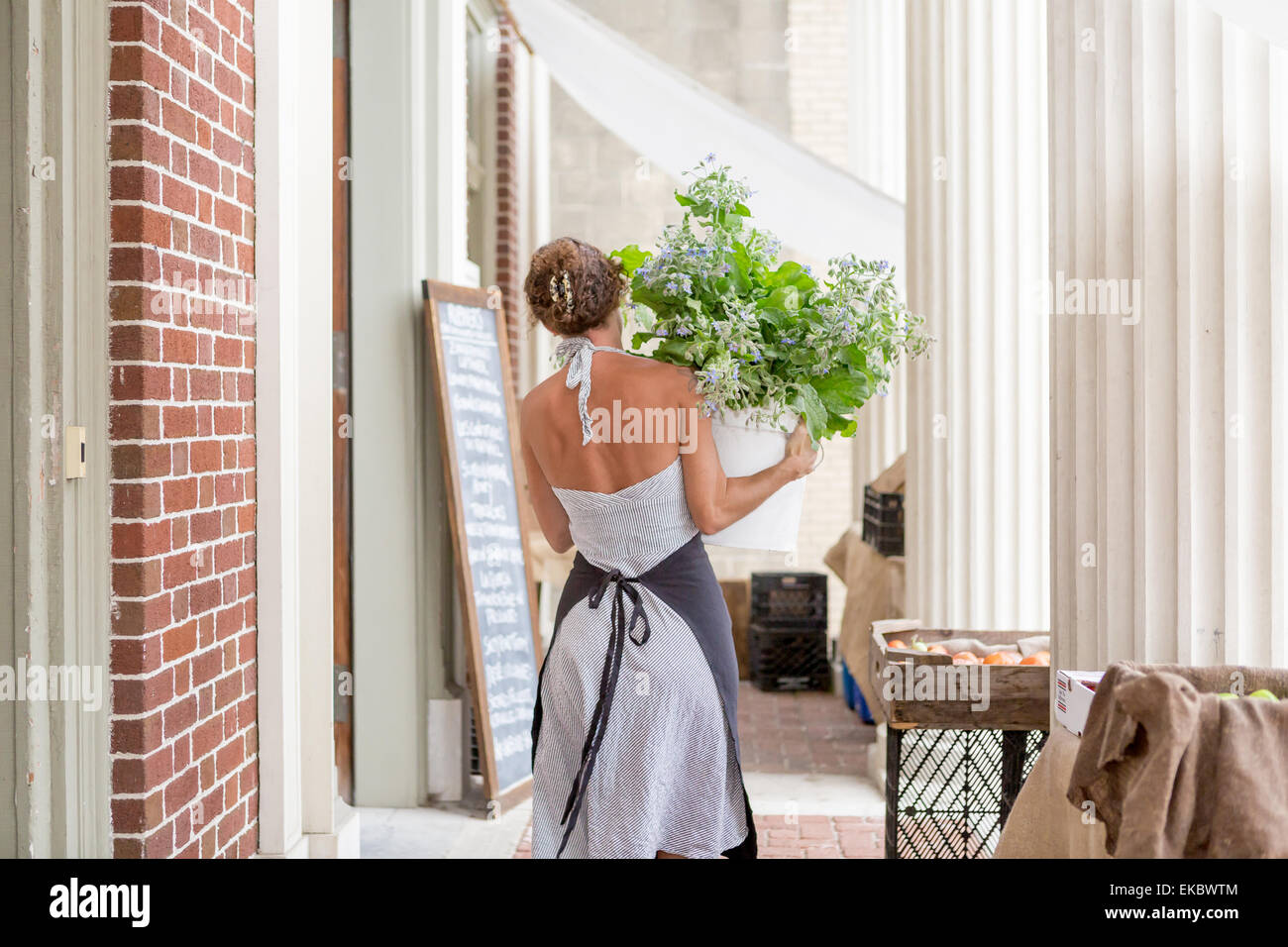 A woman unloads organic goods outside a grocery store - Stock Image