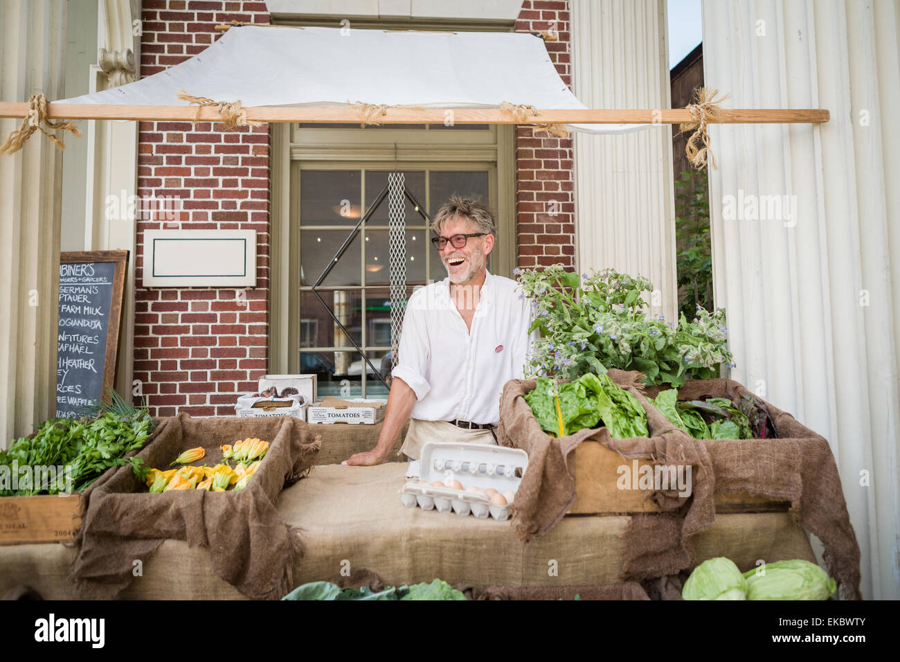 Farmer selling organic eggs and vegetables on stall outside store - Stock Image