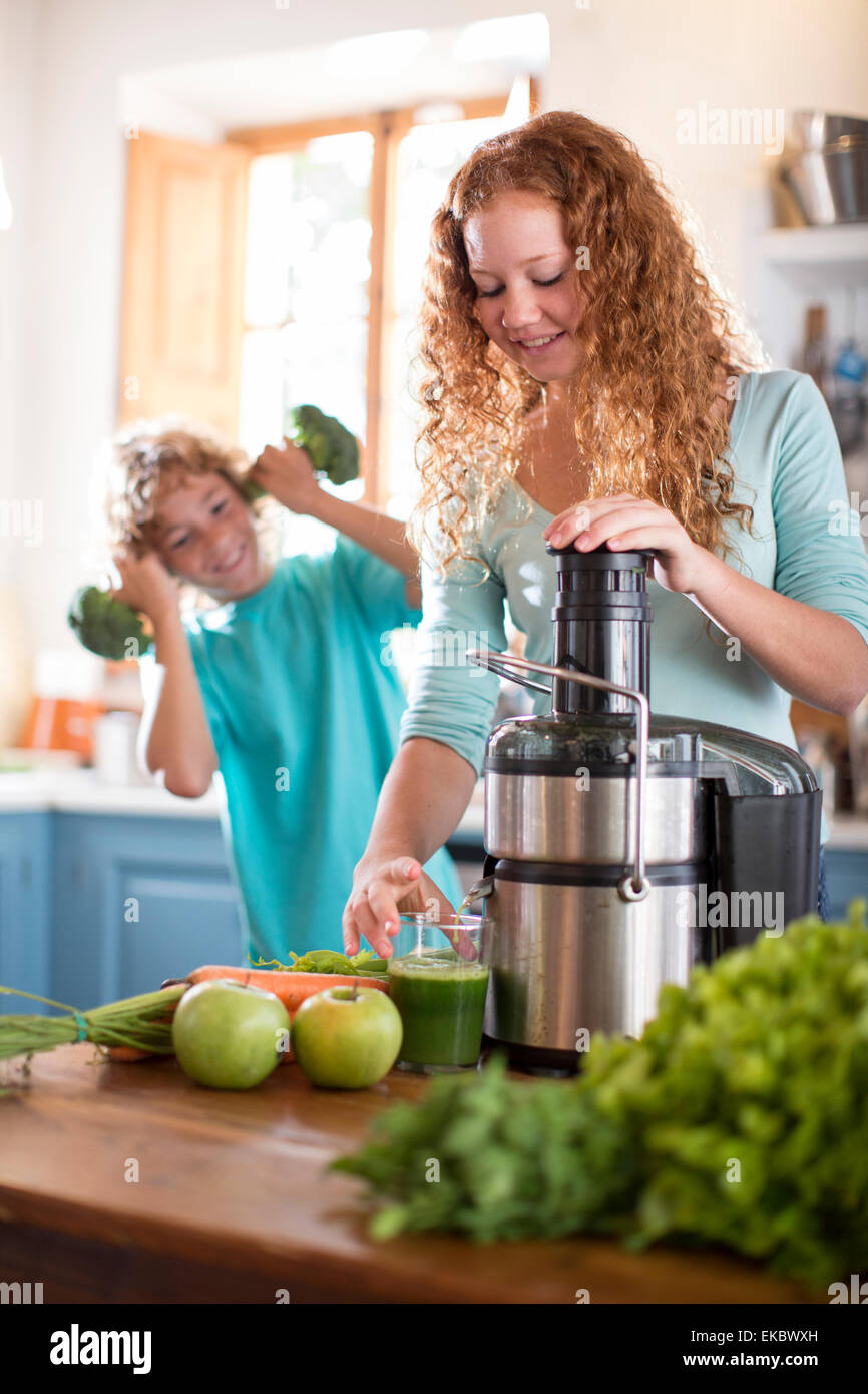 Sister blending fruit, brother playing with broccoli in background - Stock Image