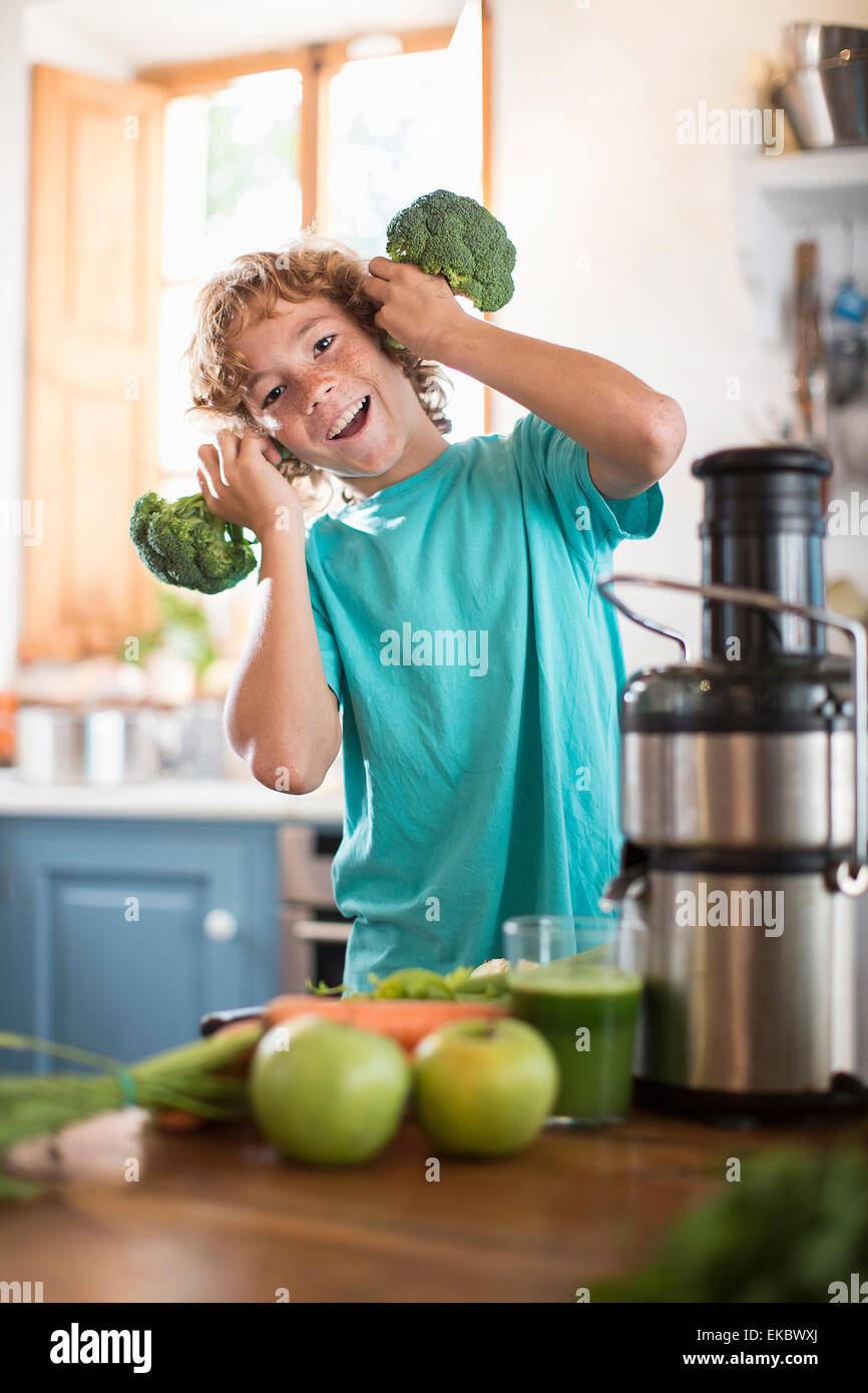 Teenage boy playing with broccoli in kitchen - Stock Image