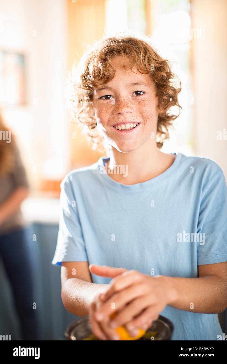 Teenage boy juicing orange in kitchen - Stock Image