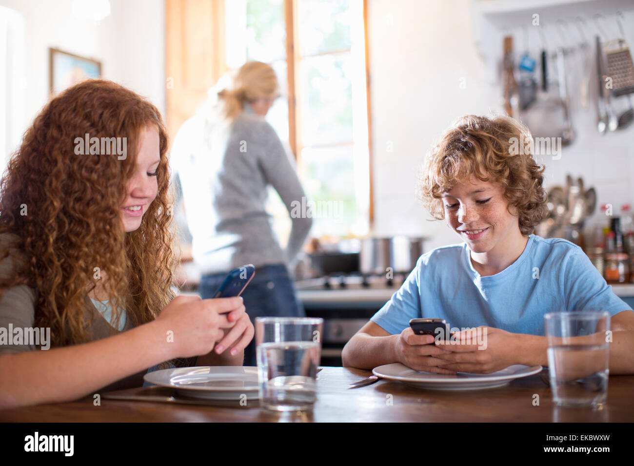 Siblings using smartphone at dining table - Stock Image
