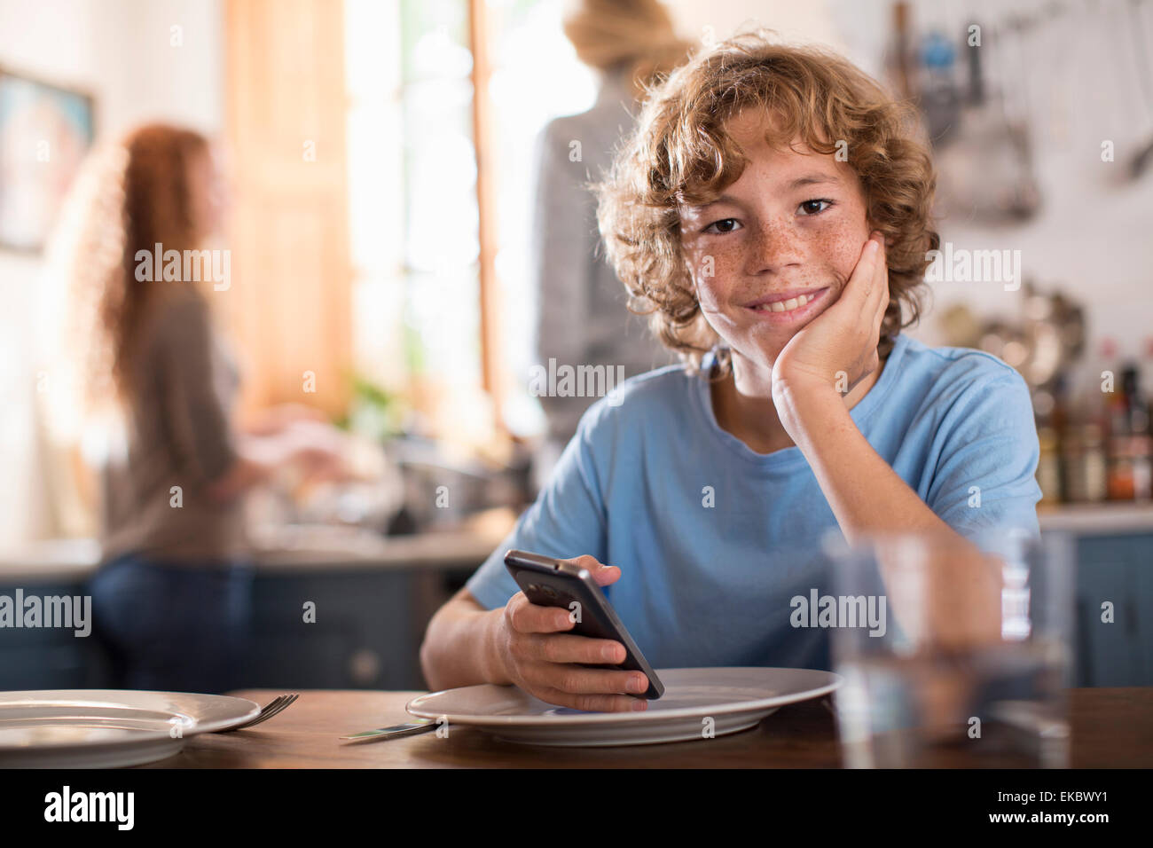 Teenage boy holding smartphone at dining table - Stock Image