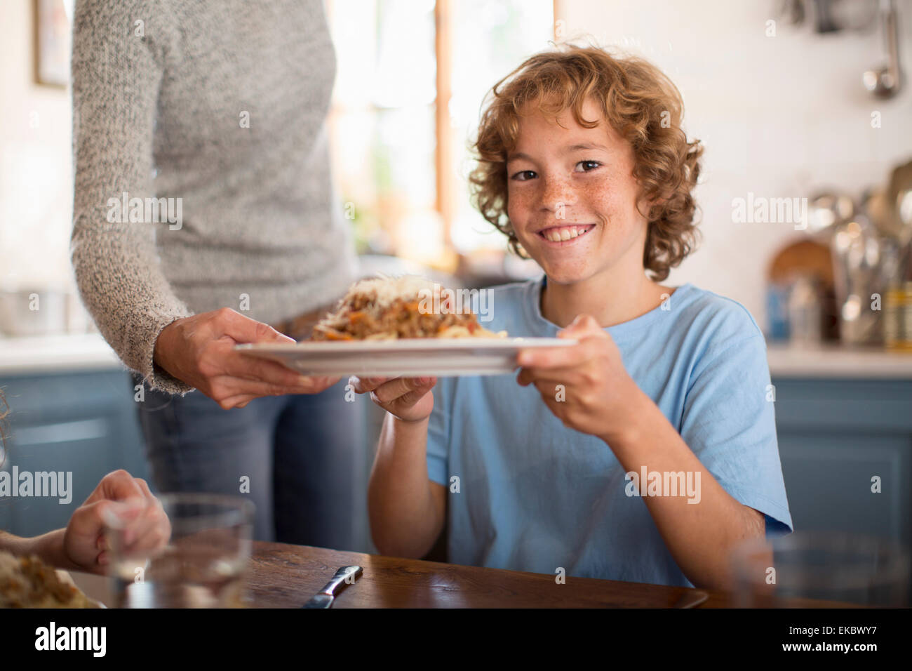 Mother serving spaghetti to children at dining table - Stock Image