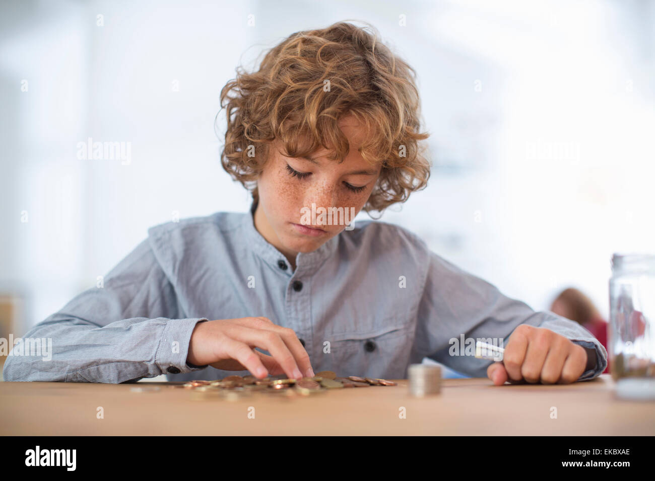 Teenage boy counting coins - Stock Image