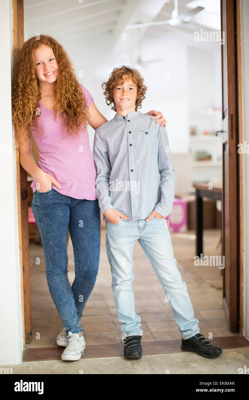 Siblings leaning against wall at entrance - Stock Image