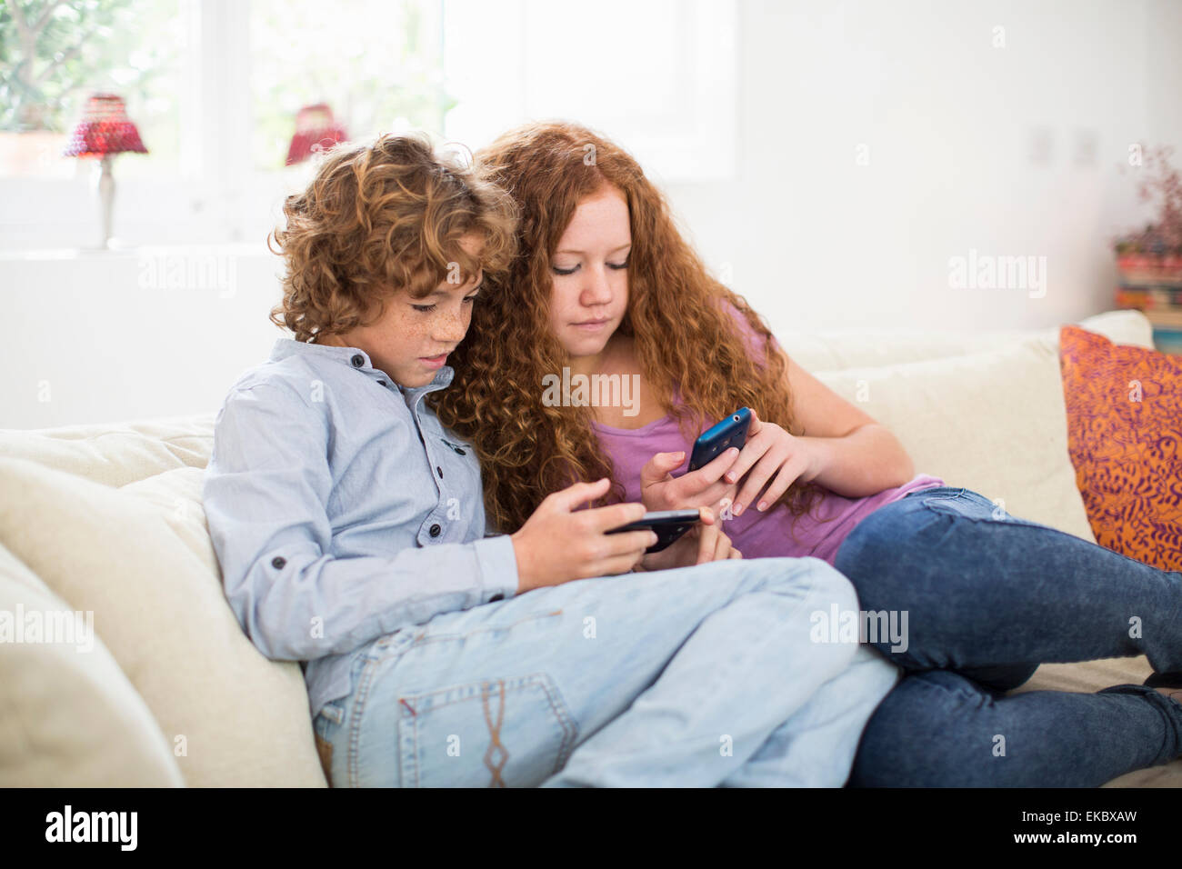 Siblings playing with handheld computer game on couch - Stock Image