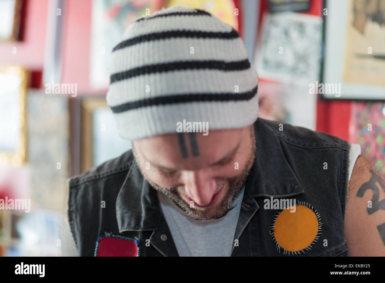 Close up of male punk shop keeper smiling and looking down in vintage toy shop - Stock Image