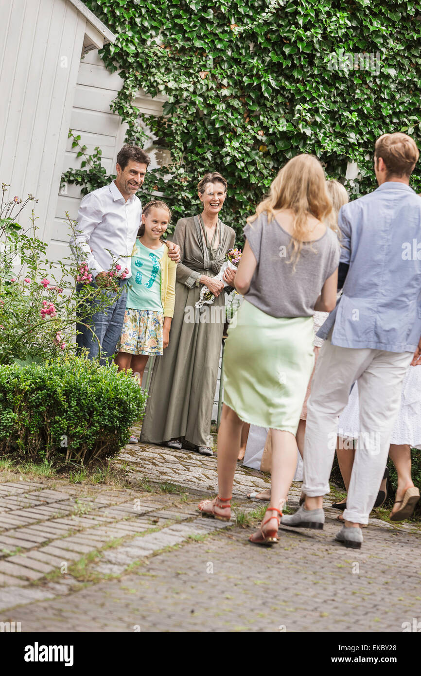 Mature couple greeting children and grandchildren in garden - Stock Image