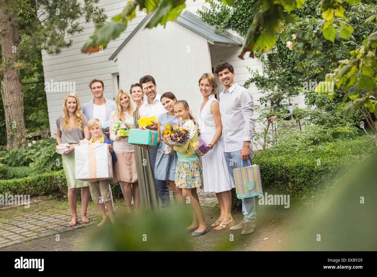 Portrait of three generation family in garden with birthday gifts - Stock Image
