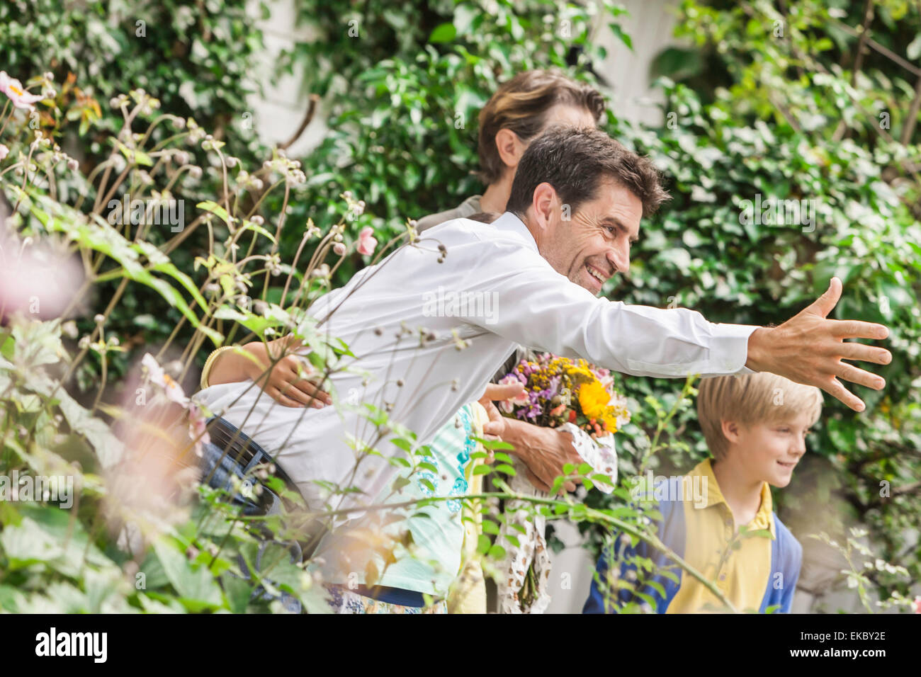 Mature couple greeting grandchildren in garden - Stock Image