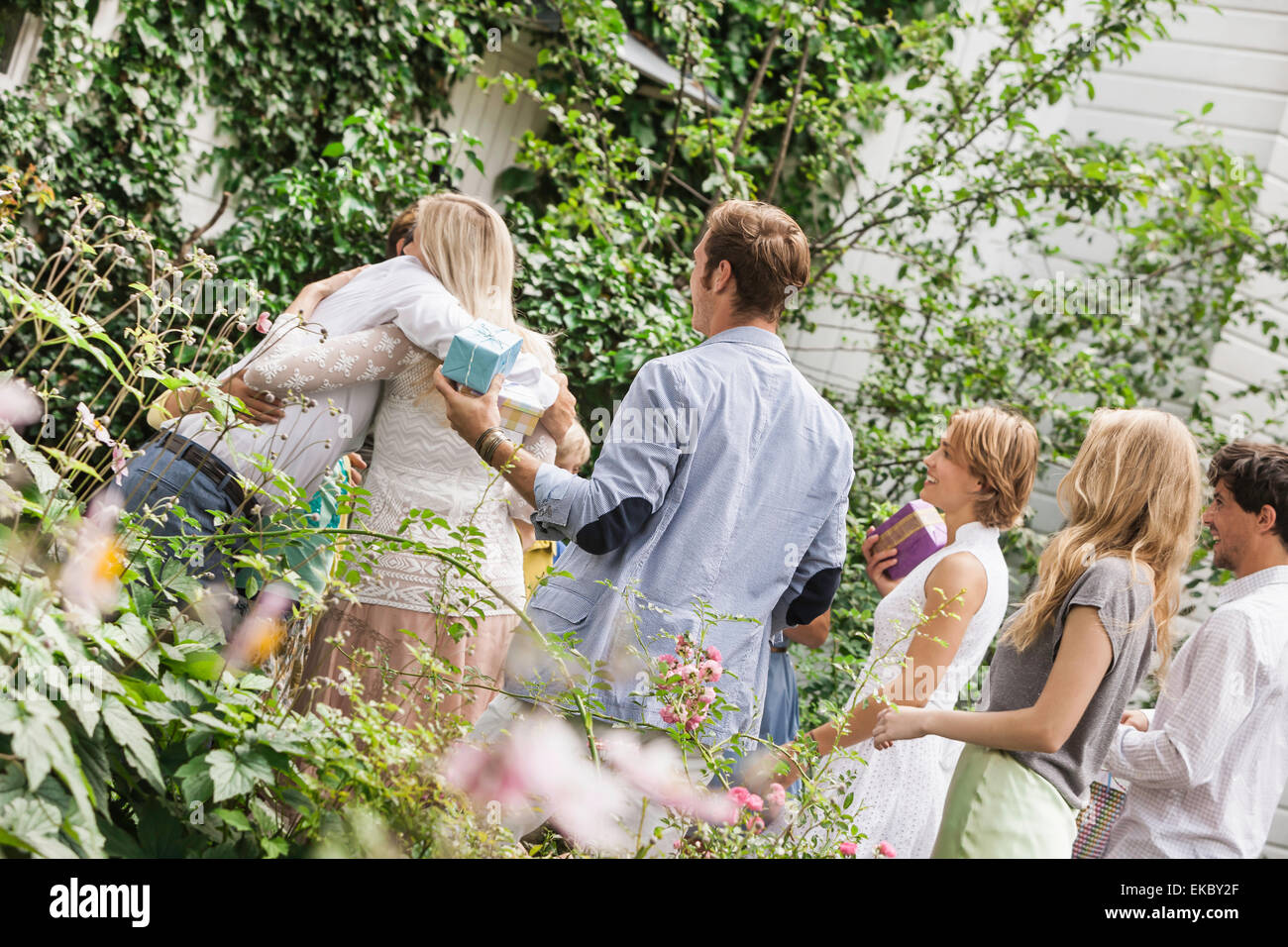 Mature couple greeting family in garden - Stock Image