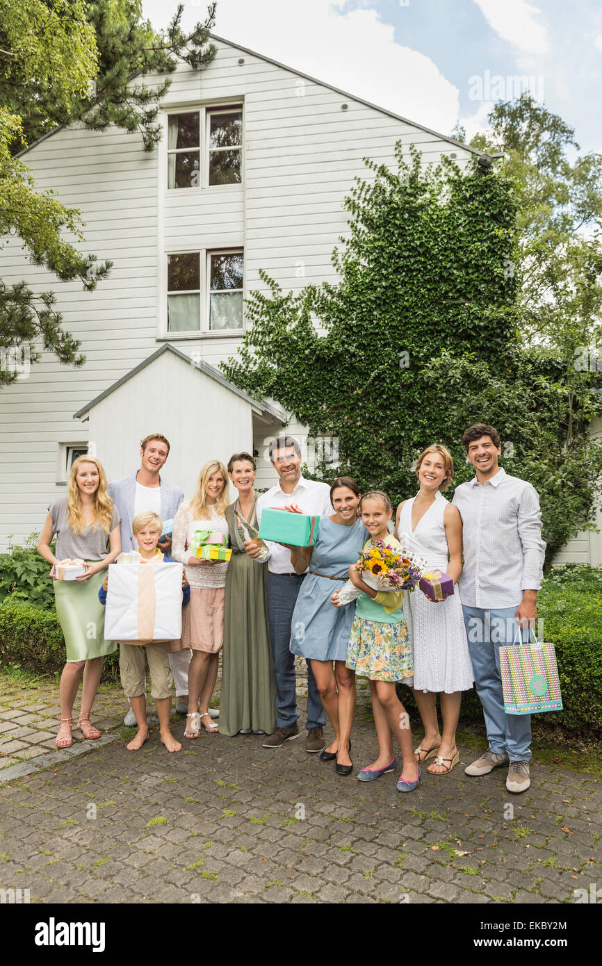 Portrait of three generation family with birthday gifts in garden - Stock Image