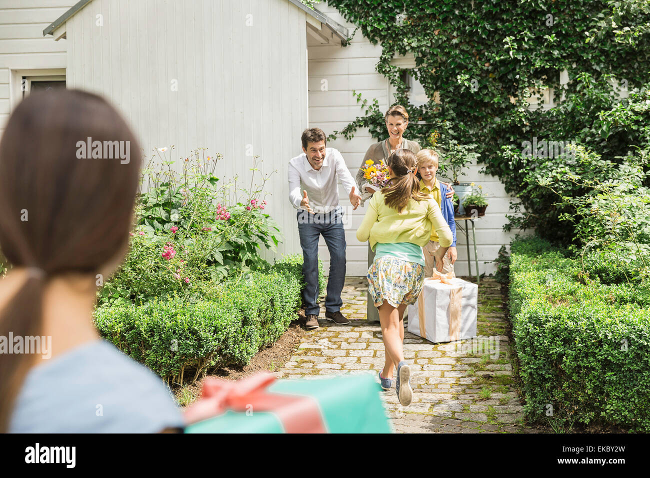Mature couple with open arms greeting family in garden - Stock Image