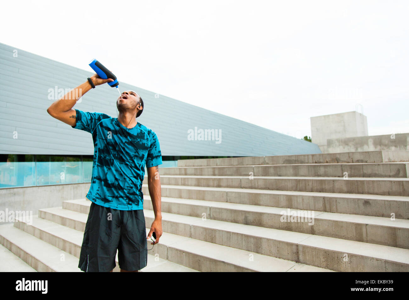 Young male runner drinking water on city steps - Stock Image