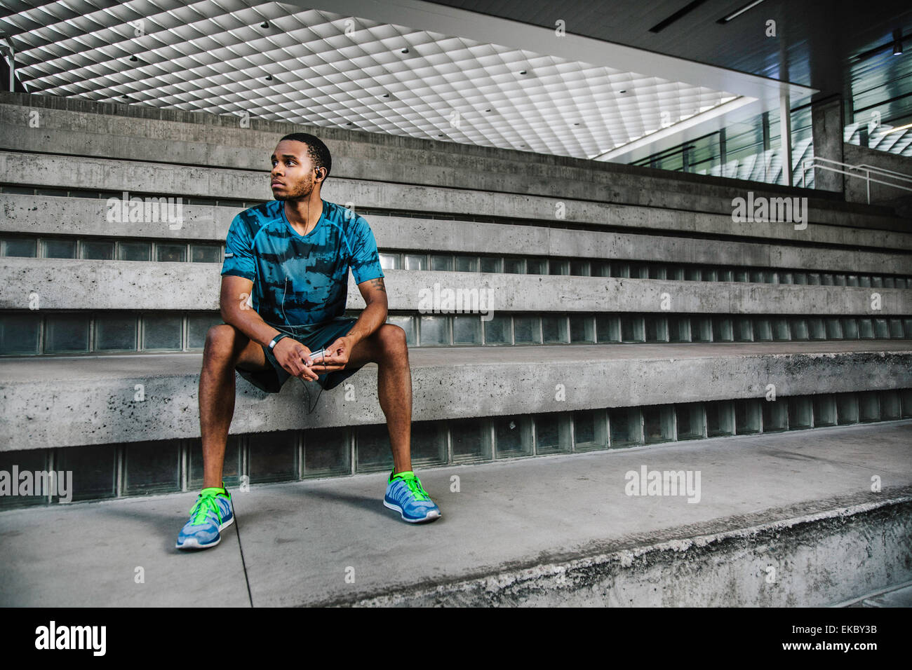 Young male runner sitting on city steps - Stock Image