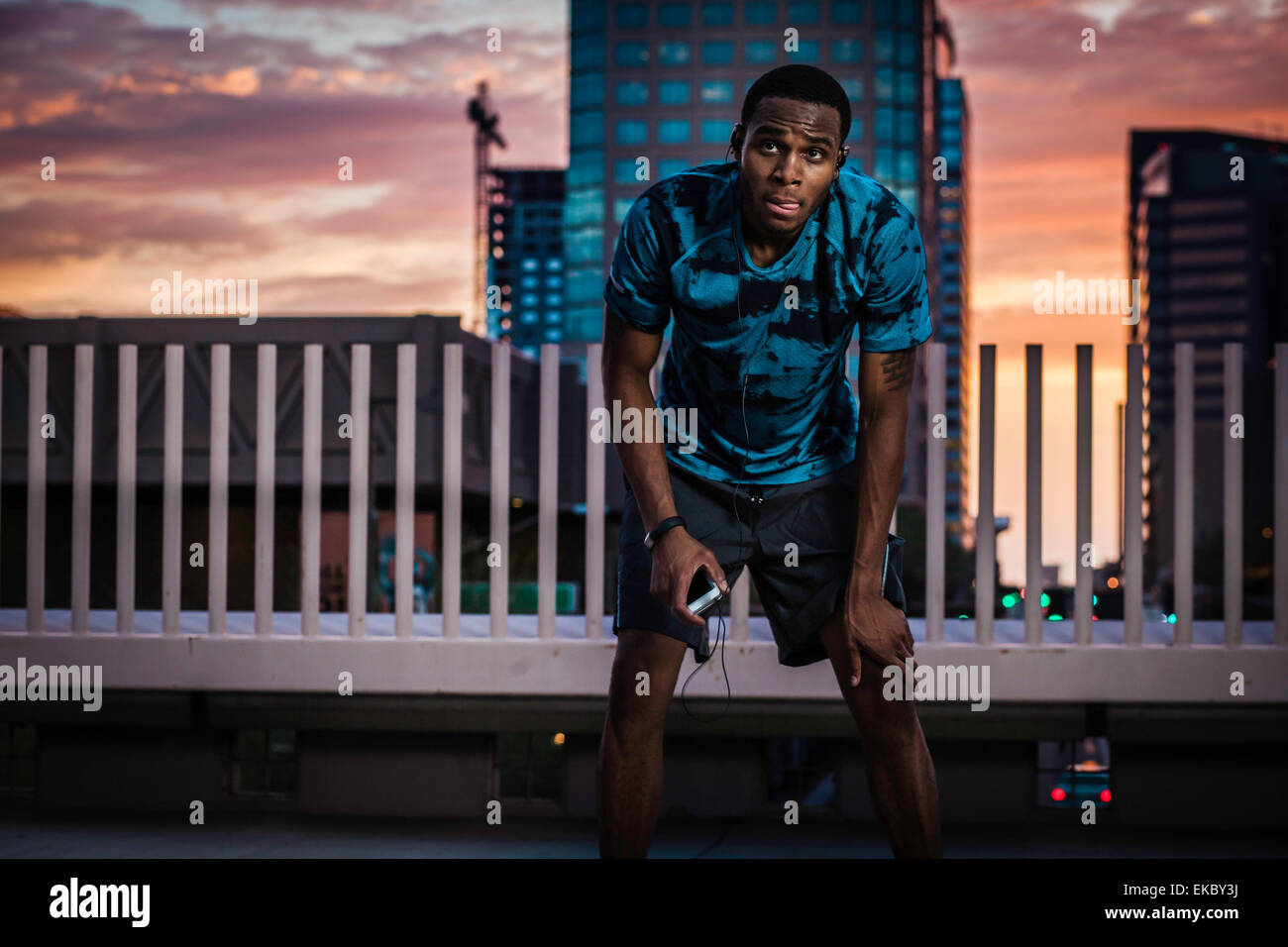 Young male runner taking a break on city roof at sunrise - Stock Image